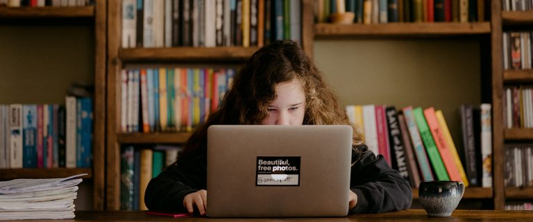 Girl on laptop in front of book shelves